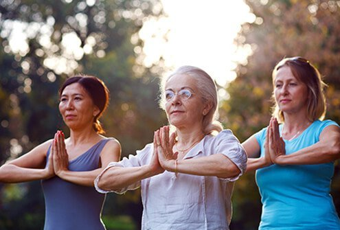 A group of women practicing yoga outside.