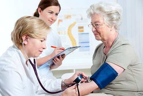 A doctor and nurse recording a senior female patient's blood pressure.