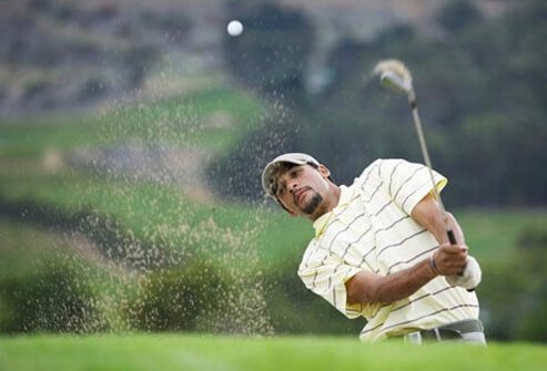 A golfer hits the ball from the bunker.