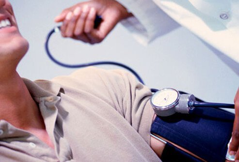 A male patient has his blood pressure checked by a doctor.