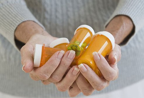 A woman holding medicine bottles.