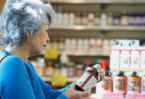A senior woman examines the back label of a supplement bottle.