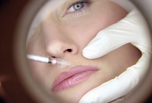 A woman receives a Botox injection to her lips.