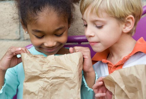 Kids eating sack lunches.