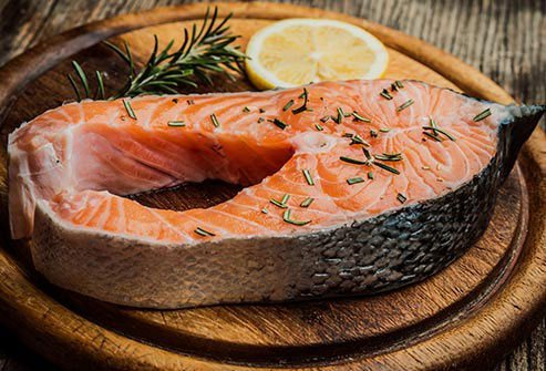 Salmon steak on a wooden plate with lemon and rosemary