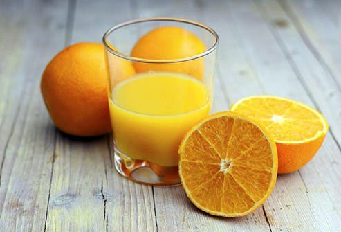 Glass of orange juice surrounded by half and whole oranges