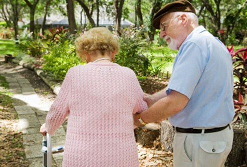 A senior couple with osteoporosis goes for a walk.
