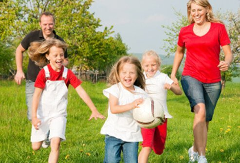 A young girl takes the ball and leads her family in some fun park activity.
