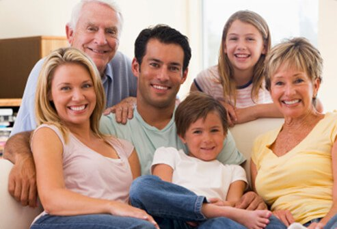 A happy extended family of grandparents, parents, and children pose for a picture.