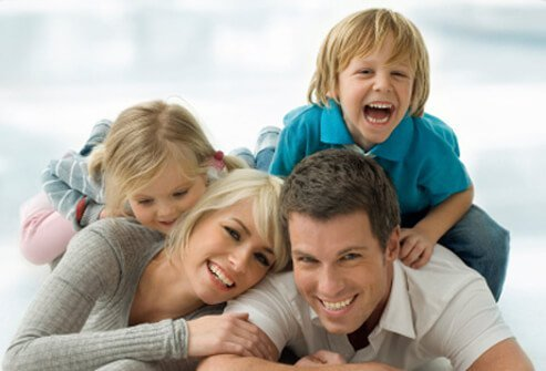 Happy parents play with their two children.