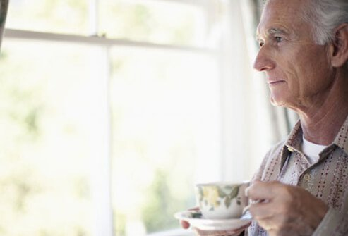 Photo of older man looking out window and drinking tea.