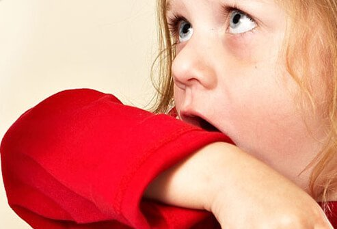 A girl with bordetella pertussis coughing into her sleeve.
