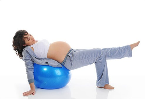 A pregnant woman performing an ankle rotation exercise on an exercise ball.