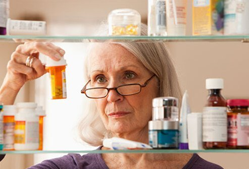 A senior woman reading the dosage of a prescription medication bottle.