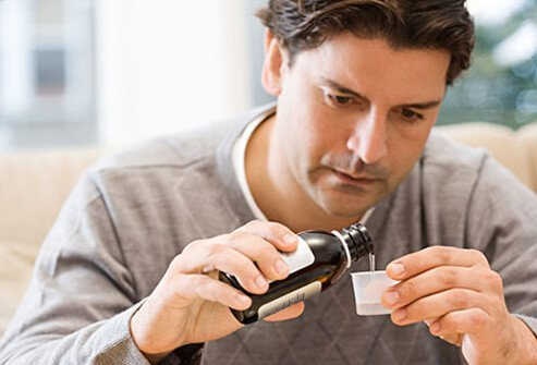 A man pours prescription cough syrup in to a cup.