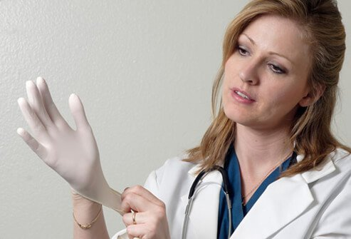 A dermatologist puts on gloves prior to an exam.