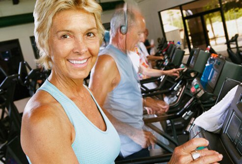 Photo of woman exercising on treadmill in a gym.