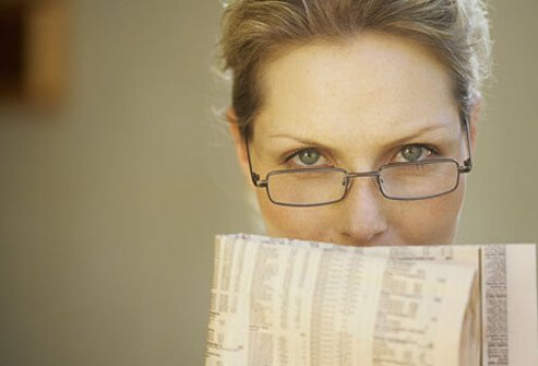 A woman wears reading glasses.