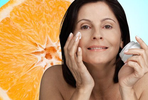 A woman smoothes vitamin c enriched cream on her face.