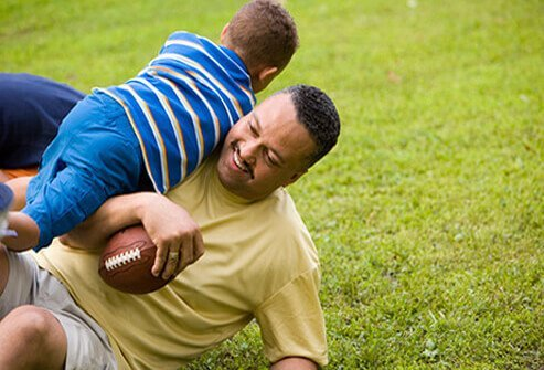 A father and son enjoy playing football in the backyard.