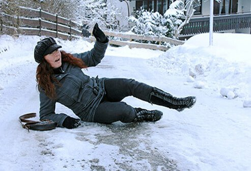 A woman slips and falls on ice.