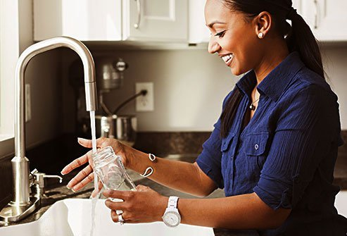 Woman washing bottle at kitchen sink.