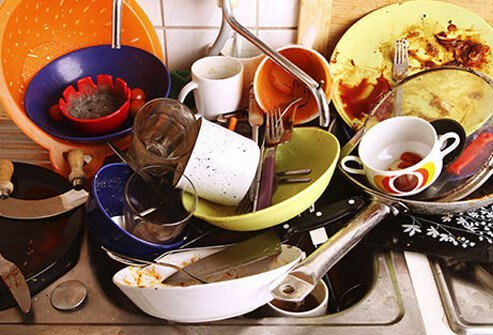Photo of dirty dishes piling up at the sink.