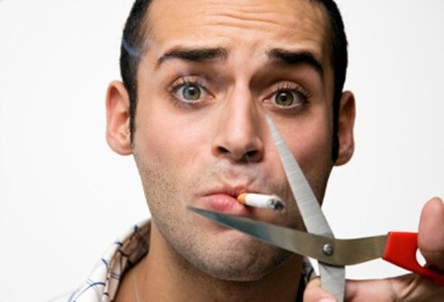 A man's cigarette about to be cut by scissors.