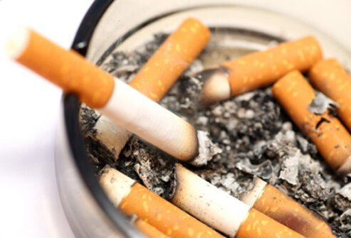 An ash tray filled with cigarettes and ash.
