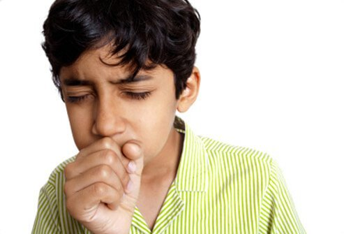 A young boy coughs.