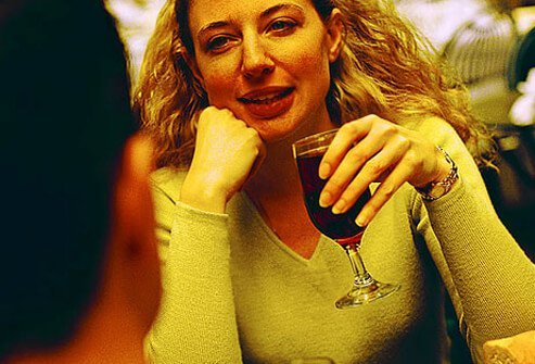 Photo of woman drinking wine in restaurant.