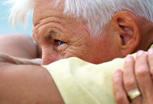 A senior man being consoled.