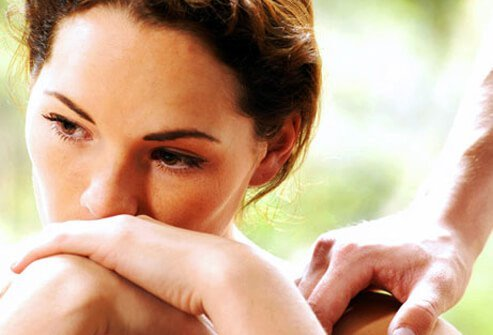 A depressed woman being consoled.