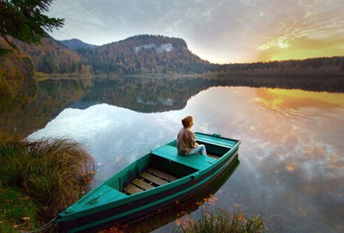 A woman in a boat looking at the sunset.