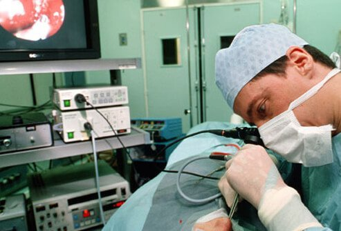 A doctor using an endoscope in the nasal cavity of patient.