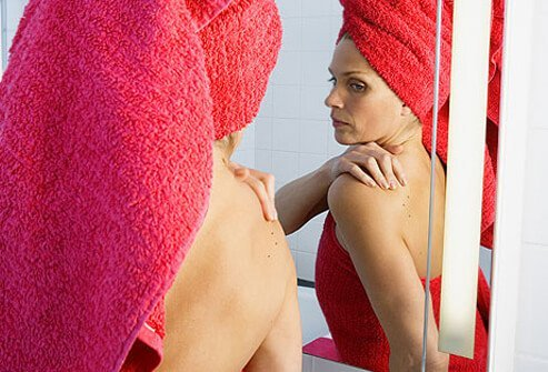 Woman in towel checking skin for moles in bathroom mirror.