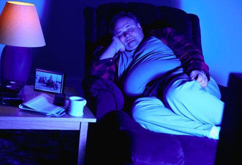 A man with poor sleep hygiene asleep in front of a television.