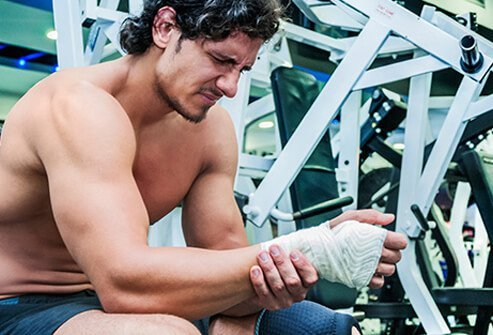 A man in the gym with a wrist injury from lifting weights.