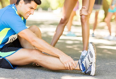 A runner on the ground suffering from a sprained ankle.
