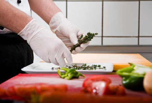A chef makes a salad while wearing rubber gloves.