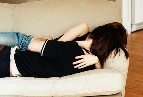 Photo of teenage couple on the couch, at risk for STDs.