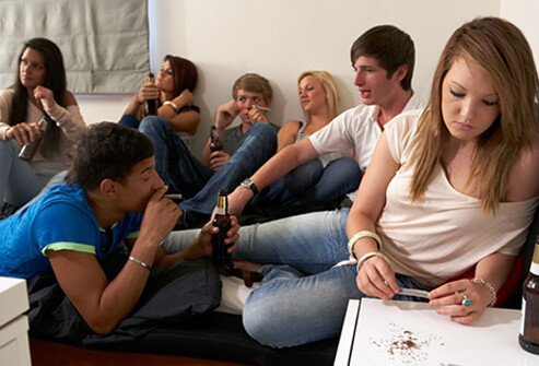 Teenagers drink and smoke at a party.