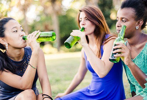 Three teenage girls drink alcohol at the park.