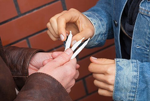 A high school student gives a marijuana joint to another student.