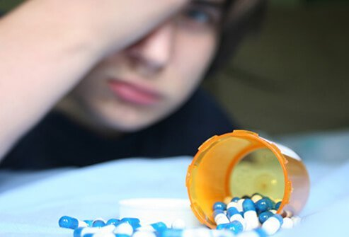 A teenage boy with spilled prescription medication on his bed.