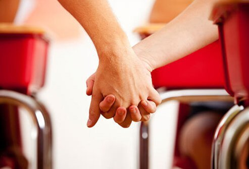 A teenage couple holds hands in class.