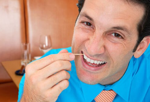 A man picking his teeth with a toothpick.