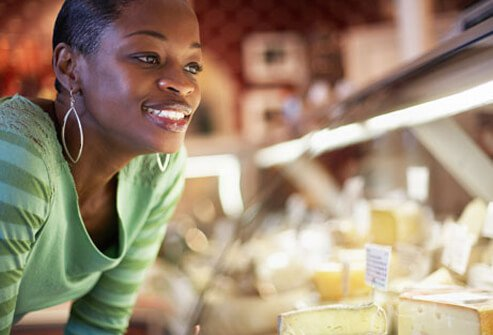 A woman looking into a cheese display case.