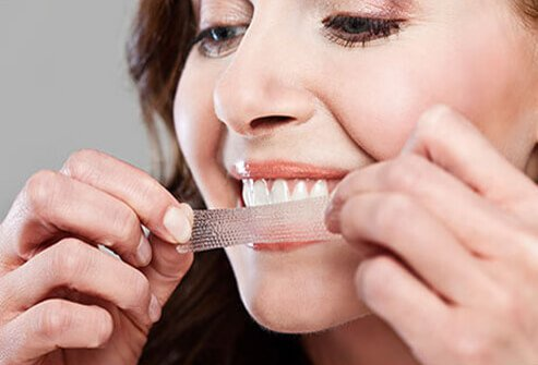 A woman applies teeth whitening strips.