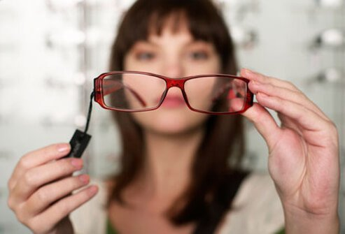 A woman trying on glasses at the optometrist because her vision has changed due to hyperthyroidism.